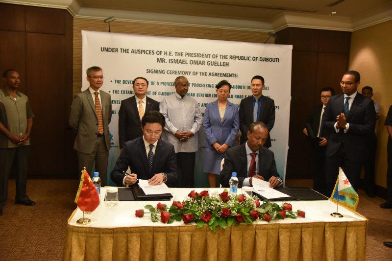 Ein Vertreter des chinesischen Konzerns IZP (links) und der Präsident der dschibutischen Zentralbank (rechts) unterschreiben die Vereinbarung am 18. Januar 2016 in Dschibuti im Beisein von Ismail Omar Guelleh ( auf im Hintergrund im hellen Hemd).