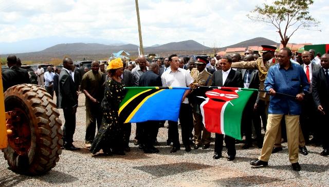 Jakaya Kikwete (links mit der tansanischen Flagge) und Uhuru Kenyatta (rechts mit der kenianischen Flagge) geben den Startschuss zum Bau der Mwatate-Taveta-Straße am 4. Oktober 2015 im kenianischen Taveta.