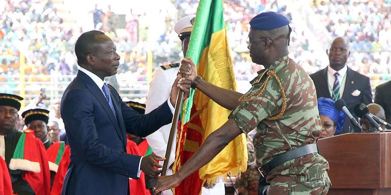 Benins neuer Staatspräsident Patrice Talon (links) nimmt am 6. April 2016 die Flagge seines Landes von einem beninischen Wehrmann entgegen.
