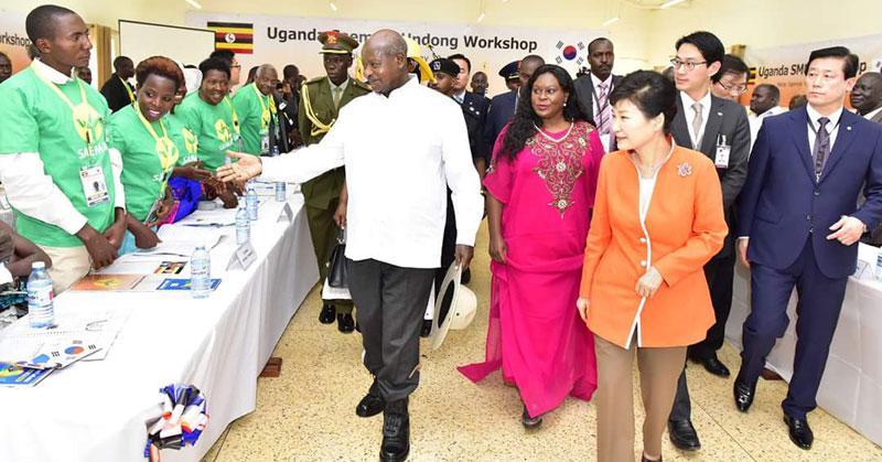 """Ugandas Staatspräsident Museveni (im weißen Hemd, mittig) und Südkoreas Staatspräsidentin Park Geun-hye ( im orangen Kleid, rechts) bei der offiziellen Eröffnung des """"National Farmers´ Leadership Center"""" (NFLC) im ugandischen Kampiringisa -- im ländlichen Bezirk Mpigi -- am 30. Mai 2016."""
